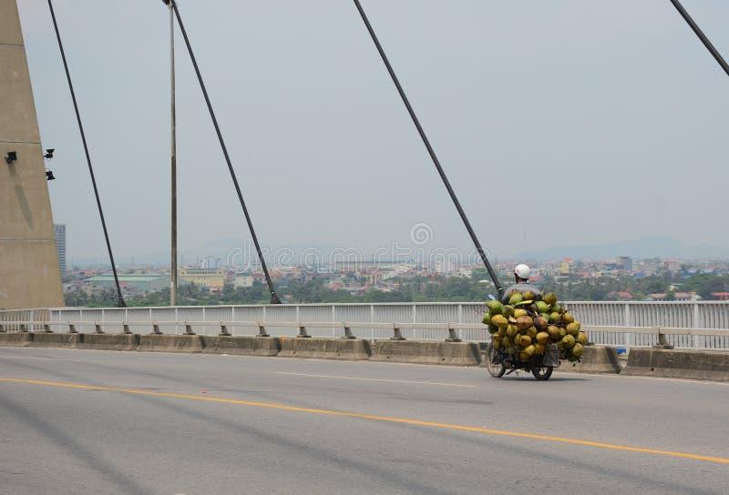 Les gens conduisant sur le pont de Binh avec le ciel nuageux photos stock
