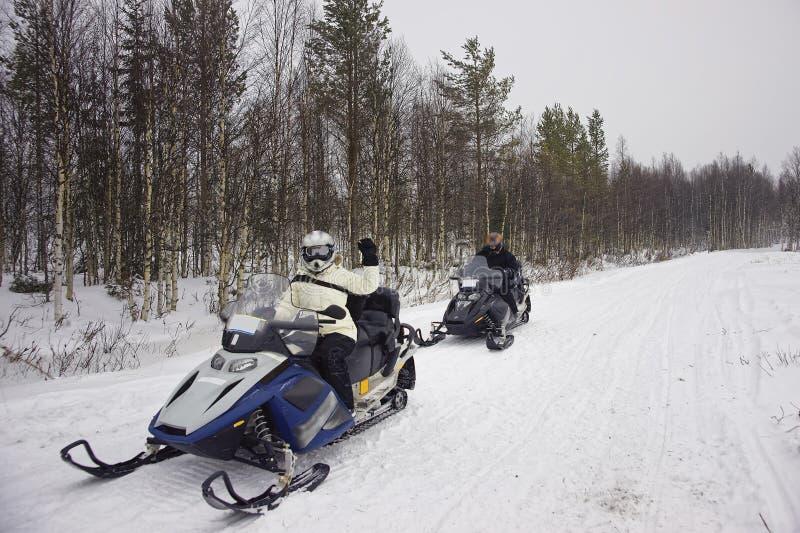 Les gens conduisant un motoneige dans Ruka en Laponie photo libre de droits