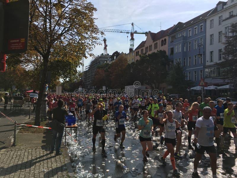 Les gens courant chez Berlin Marathon au-dessus des tonnes de tasses en plastique vides photo stock