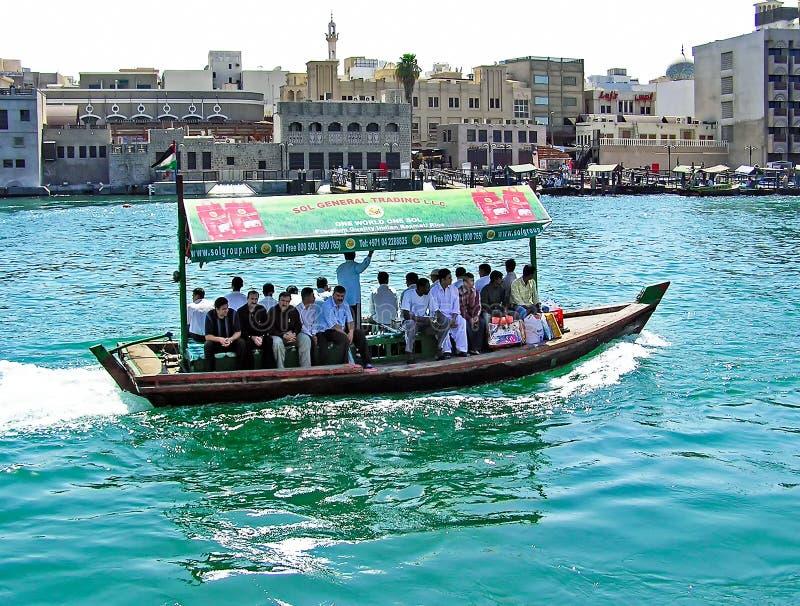 Les gens croisent le Dubai Creek entre les secteurs de Deira et le bureau Dubaï à bord d'un taxi traditionnel de l'eau d'Abra photos stock