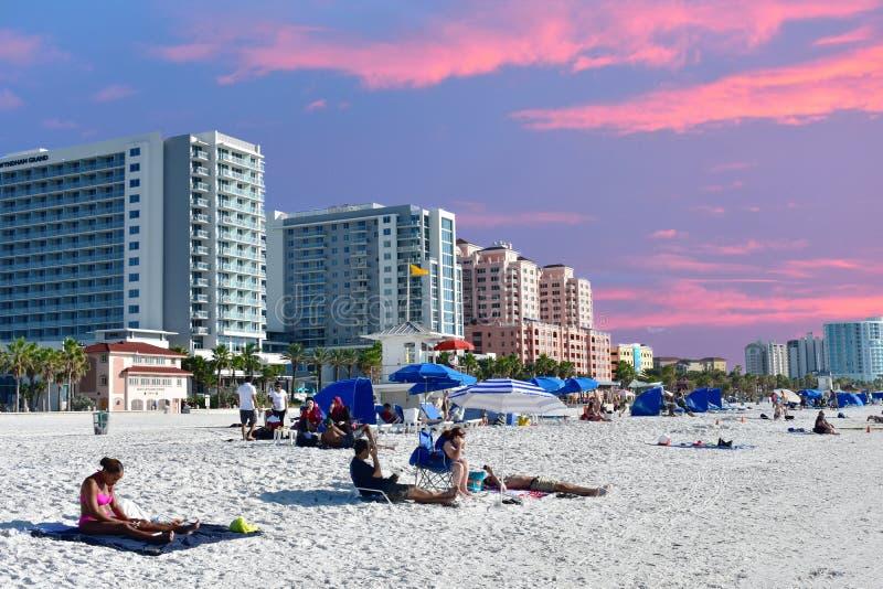 Les gens détendant à la plage sur le fond coloré de coucher du soleil images libres de droits