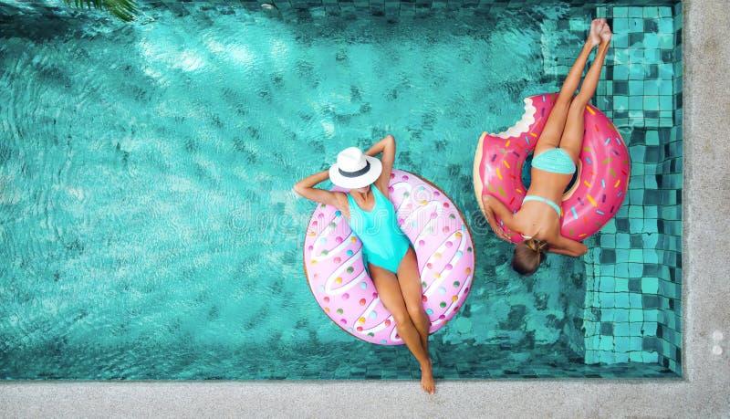 Les gens détendant sur l'anneau gonflable dans la piscine photographie stock libre de droits