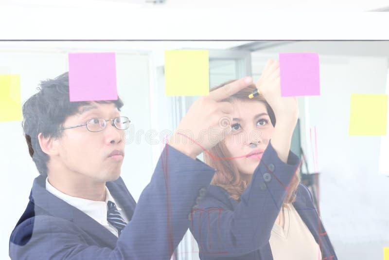 Les gens d'affaires asiatiques emploient des notes de post-it sur le mur de verre pour partager l'id?e au lieu de r?union travail images libres de droits