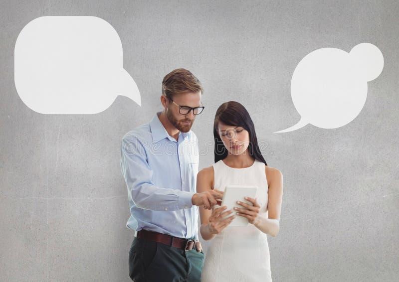 Les gens d'affaires avec la parole bouillonnent regardant un comprimé sur le fond gris photo stock