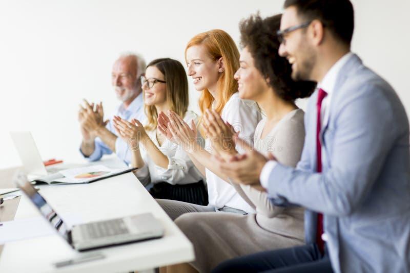 Les gens d'affaires multiraciaux battent un des mains du ` s dans le bureau image libre de droits