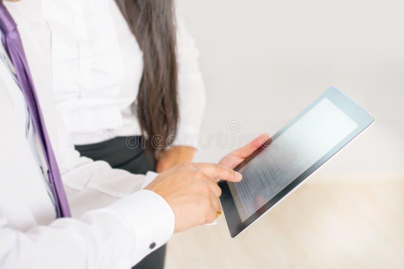 Les gens d'affaires se sont habillés dans le blanc utilisant le PC de comprimé au bureau photos libres de droits