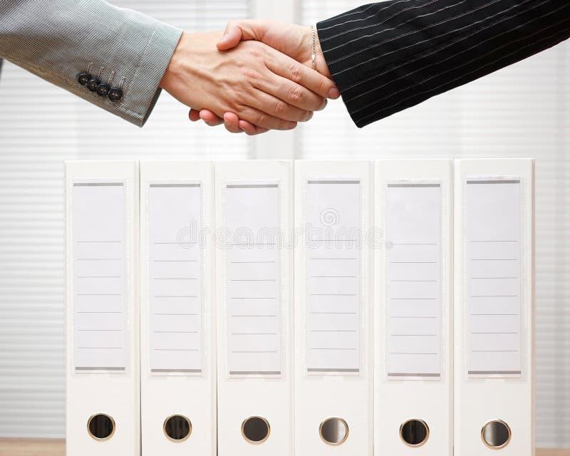 Les gens d'affaires sont poignée de main au-dessus de concept de reliures, d'affaires et de comptabilité photographie stock