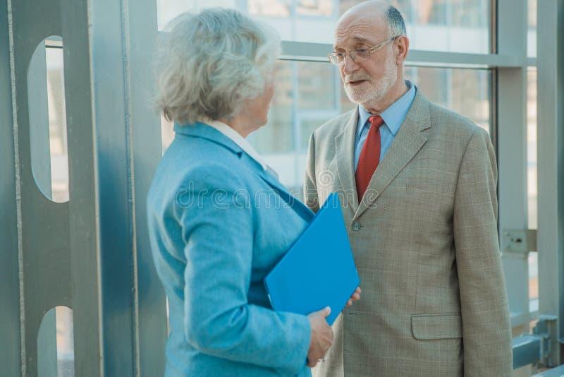 Les gens d'affaires supérieurs discutent des documents photo stock