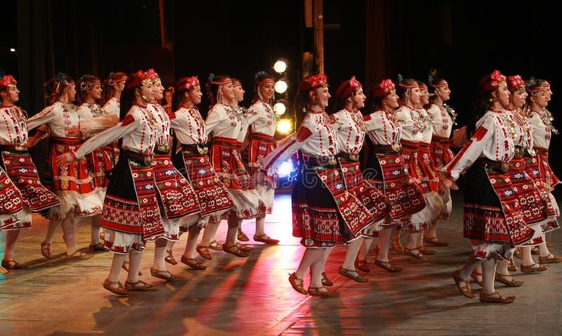 Les gens dans des costumes traditionnels de folklore exécutent le horo bulgare de danse folklorique sur la foire nationale de fol images stock