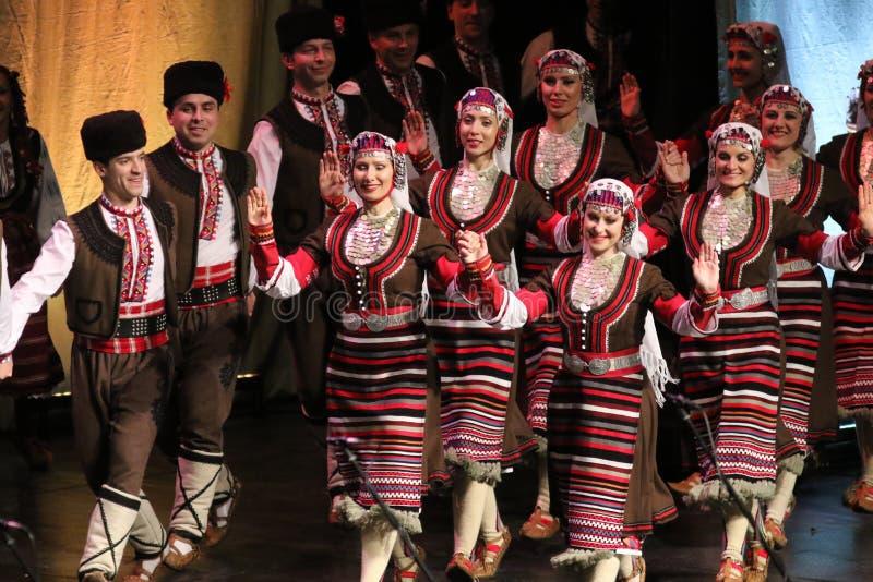 Les gens dans des costumes traditionnels de folklore ex?cutent la danse folklorique Horo bulgare image stock