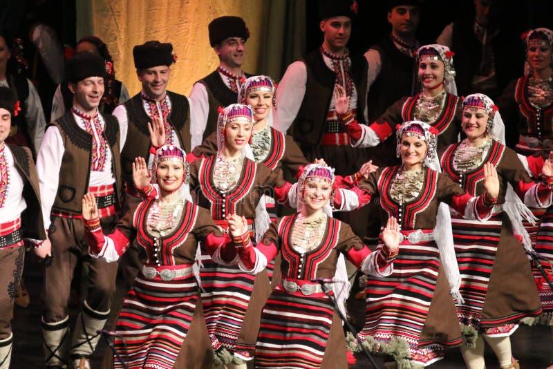 Les gens dans des costumes traditionnels de folklore ex?cutent la danse folklorique Horo bulgare image libre de droits