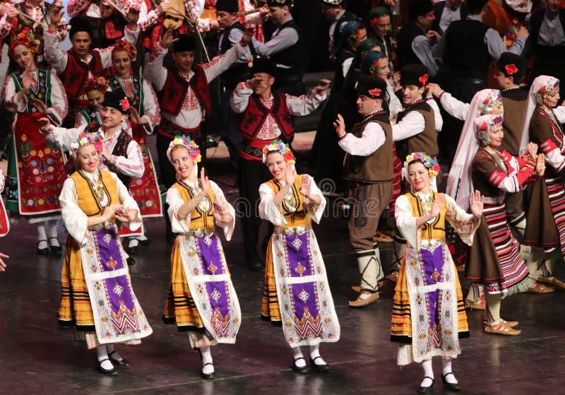 Les gens dans des costumes traditionnels de folklore ex?cutent la danse folklorique Horo bulgare photos stock