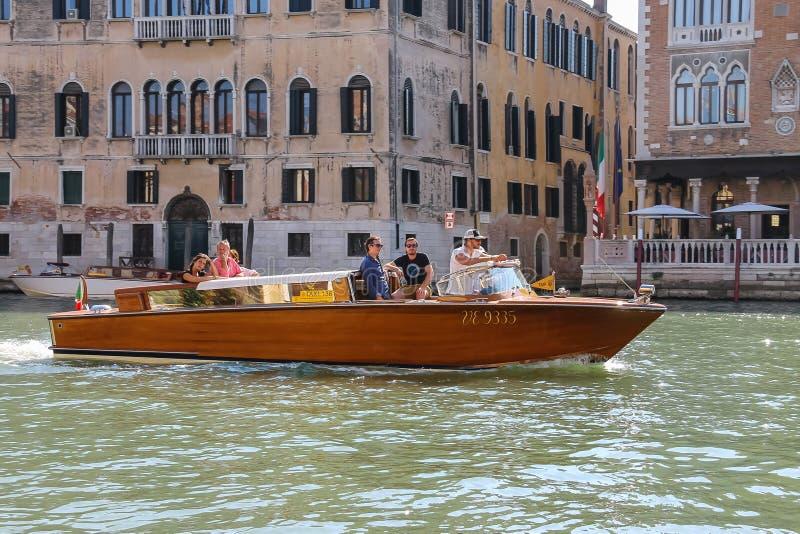Les gens dans le bateau de taxi sur le canal de Venise, Italie photographie stock libre de droits
