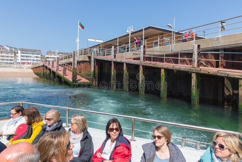 Les gens dans le ferry quittant le port Helgoland à la dune opposée d'île photographie stock libre de droits