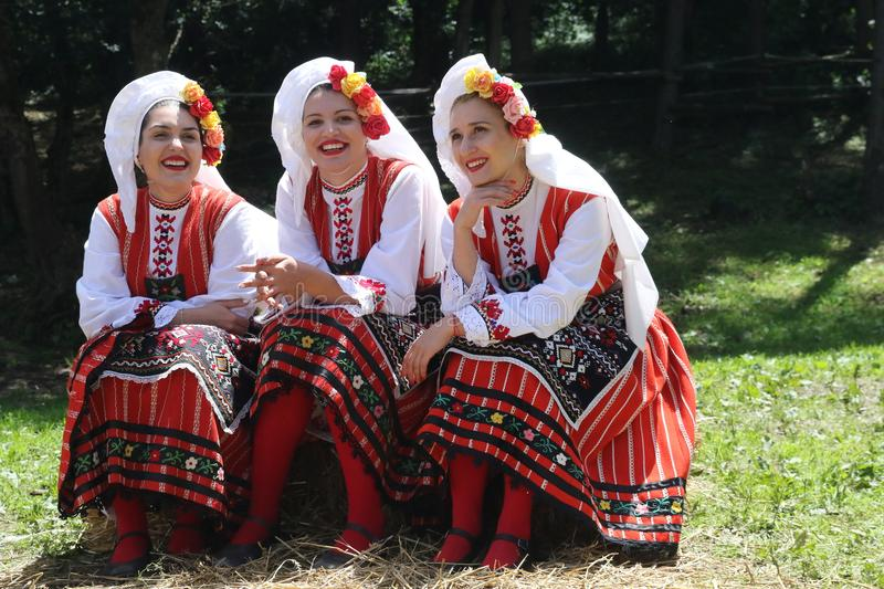 Les gens dans le folklore authentique traditionnel costument un pré près de Vratsa, Bulgarie image stock