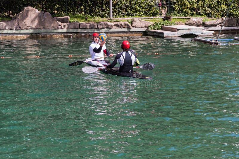 Les gens dans le kayak jouant le polo à l'étang image stock