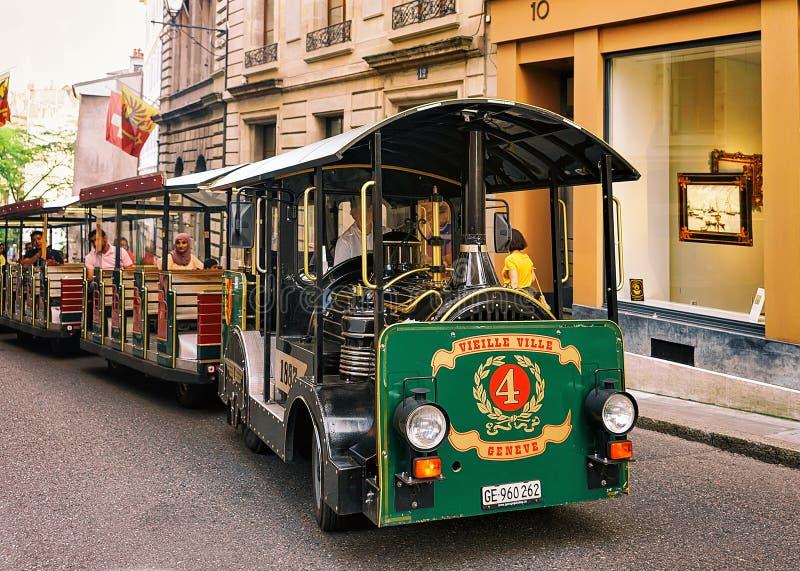 Les gens dans le tram d'excursion à la rue avec des drapeaux à Genève photos stock