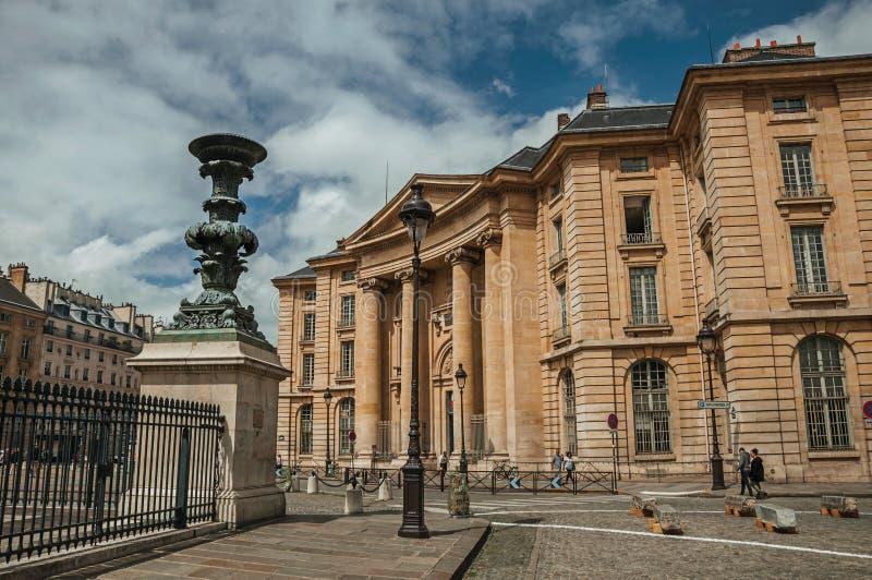 Les gens devant le bâtiment néoclassique, la barrière de fer et le ciel bleu à Paris photo stock