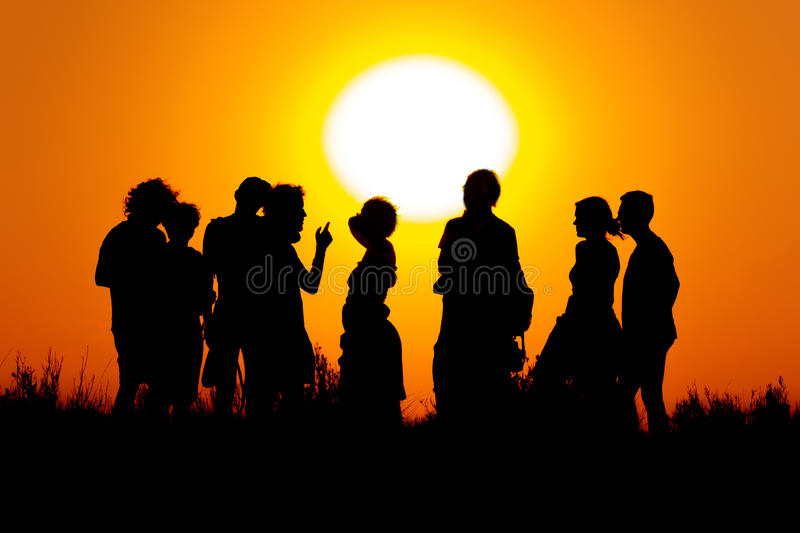 Les gens devant un coucher du soleil image stock