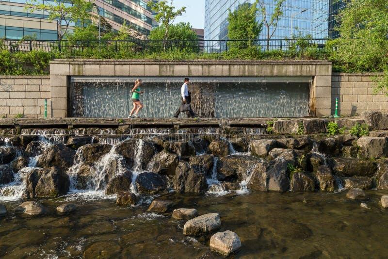 Les gens devant une cascade le long du Cheonggyecheon coulent photos libres de droits