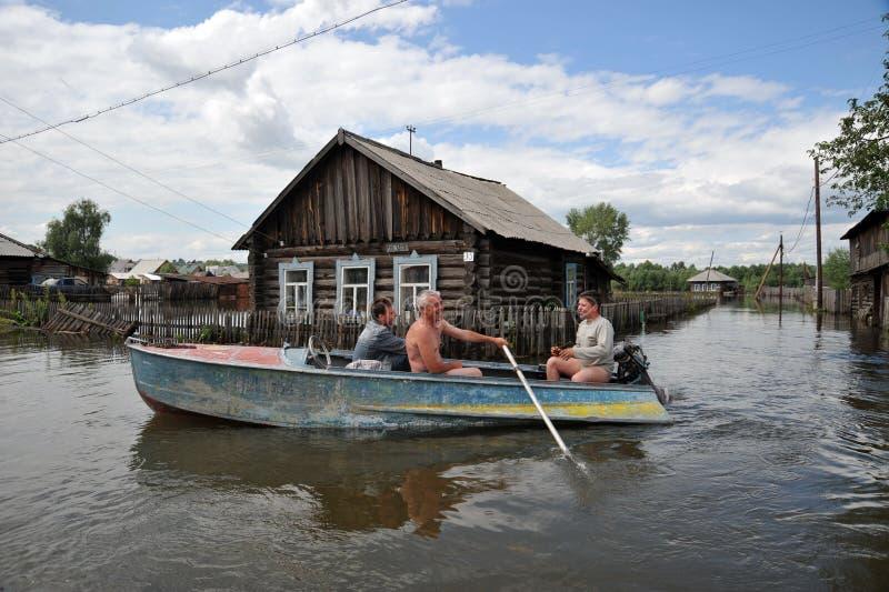 Les gens du pays se déplacent autour des rues en bateau Le fleuve Ob, qui est sorti des banques, a inondé les périphéries de la v photos libres de droits