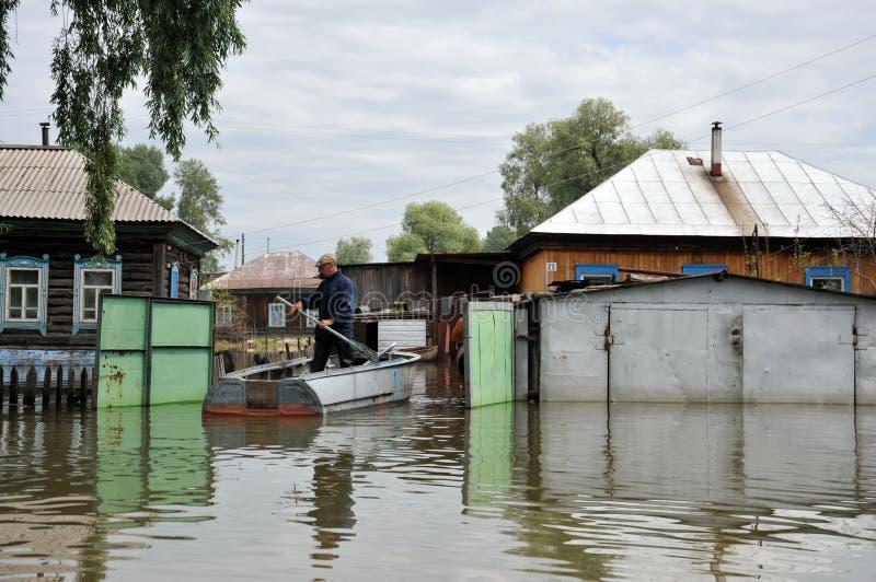 Les gens du pays se déplacent autour des rues en bateau Le fleuve Ob, qui est sorti des banques, a inondé les périphéries de la v photo libre de droits