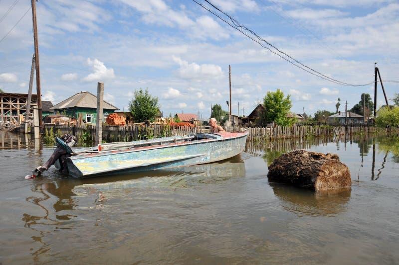 Les gens du pays se déplacent autour des rues en bateau Le fleuve Ob, qui est sorti des banques, a inondé les périphéries de la v photographie stock