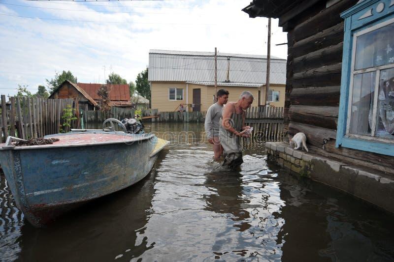 Les gens du pays se déplacent autour des rues en bateau Le fleuve Ob, qui est sorti des banques, a inondé les périphéries de la v image libre de droits