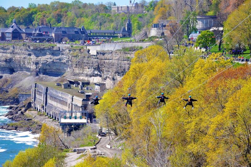 Les gens employant la ligne attraction de fermeture éclair au-dessus des chutes du Niagara photo stock