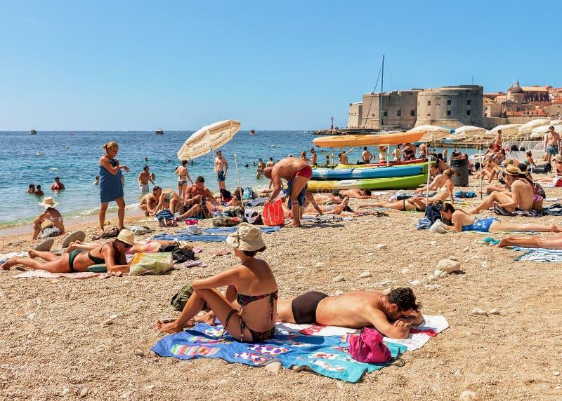Les gens en plage et la forteresse de Dubrovnik en Mer Adriatique photo stock
