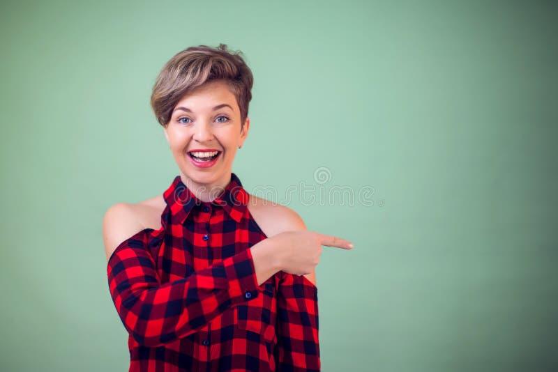 Les gens et les émotions - un point de femme se demandante de portrait avec un doigt sur quelque chose photos stock