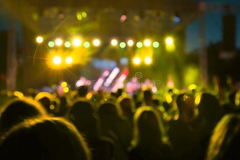 Les gens et le bokeh jaune de lumières de concert images stock