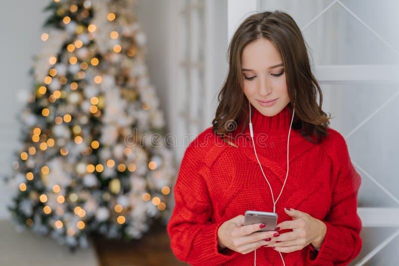 Les gens et le concept de vacances La jeune femme d'une chevelure foncée concentrée tient le téléphone portable dans des mains, l photo libre de droits