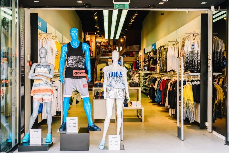 Les gens faisant des emplettes et passant en revue dans le magasin local de vêtements photos libres de droits