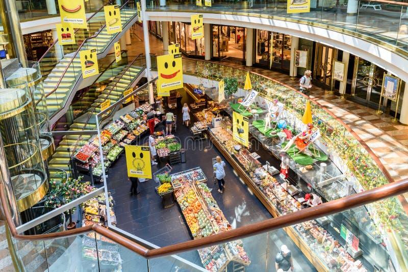 Les gens faisant des emplettes pour la nourriture d'épicerie dans le bas-côté de magasin de supermarché photographie stock