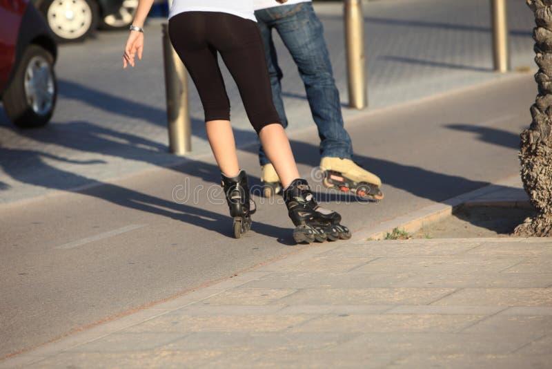 Les gens faisant du roller en bas d'un trottoir photo stock