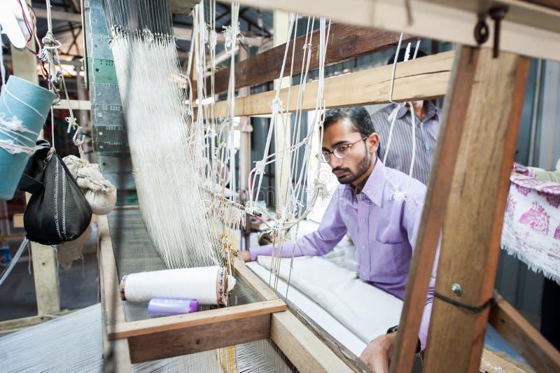 Les gens faisant le tissu coloré de fil en soie par le métier à tisser de tissage indien images stock