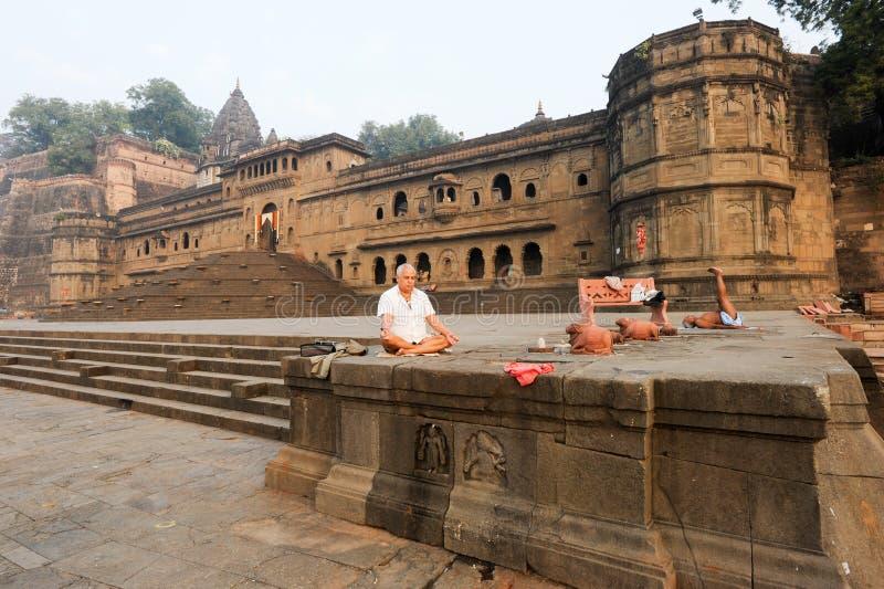 Les gens faisant le yoga et la méditation devant le palais de Maheshwar photographie stock