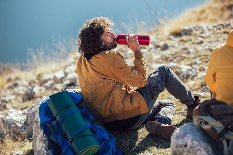 Les gens faisant une pause, d?tendant pendant une hausse L'eau de boissons d'homme photos libres de droits