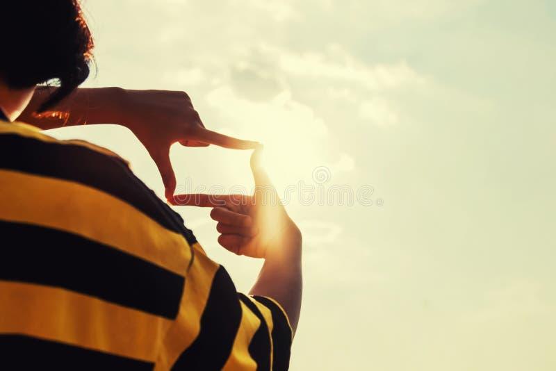 les gens font la main encadrant semblant le lever de soleil éloigné de vue Concept d'affaires photo libre de droits