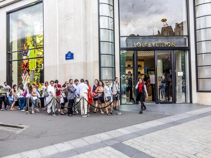 Les gens font la queue devant la boutique de Louis Vuitton photo stock