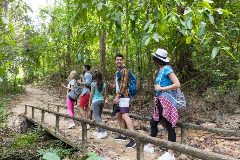 Les gens groupent avec des sacs à dos marchant sur le trekking de pont sur Forest Path, les jeunes hommes et la femme sur la haus photographie stock libre de droits
