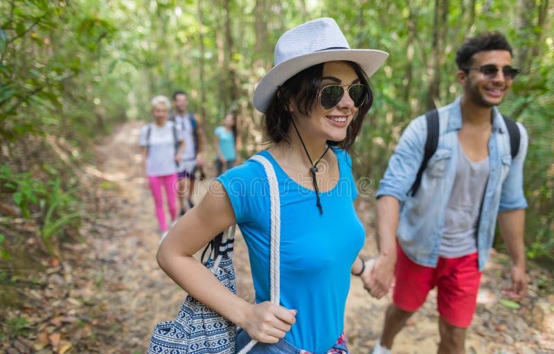 Les gens groupent avec le trekking de sacs à dos sur Forest Path, les jeunes hommes de course de mélange et la femme sur des tour photographie stock