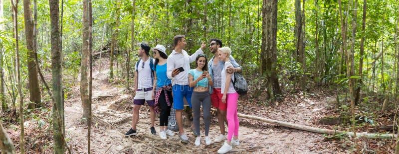 Les gens groupent avec le trekking de sacs à dos sur la carte, les jeunes hommes et la femme de téléphone de Forest Path Using Ce photos stock