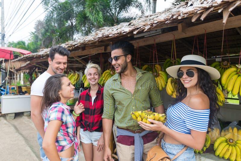 Les gens groupent les bananes de achat sur le marché de rue, le jeune homme et les voyageuses traditionnels de femme photographie stock libre de droits