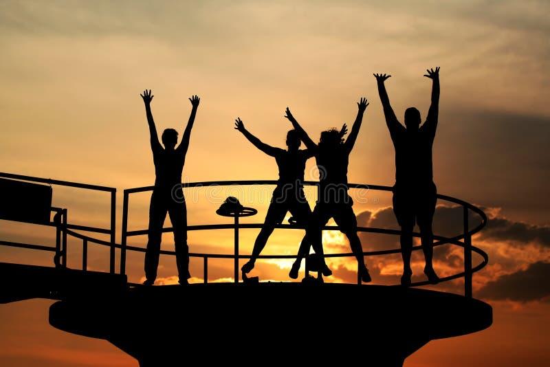 Les gens heureux sautent des silhouettes photo libre de droits