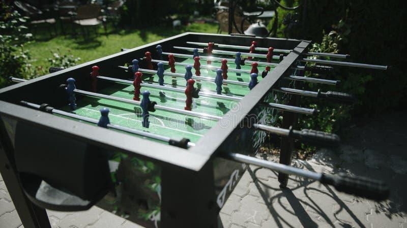 Les gens jouant le plan rapproché du football de table dehors images libres de droits