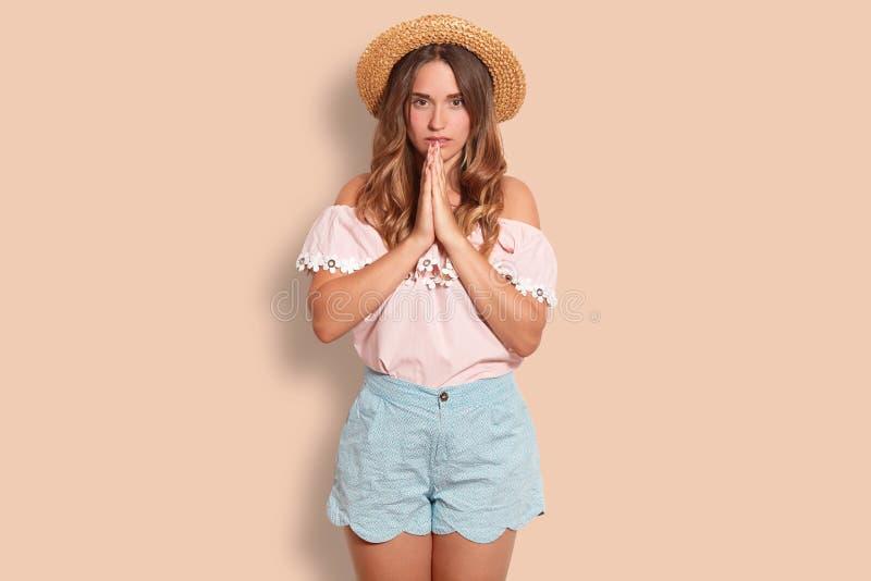 Les gens, le repos et le concept de foi La jeune femelle concentrée avec l'expression sûre, maintient des mains dans le geste de  photos stock