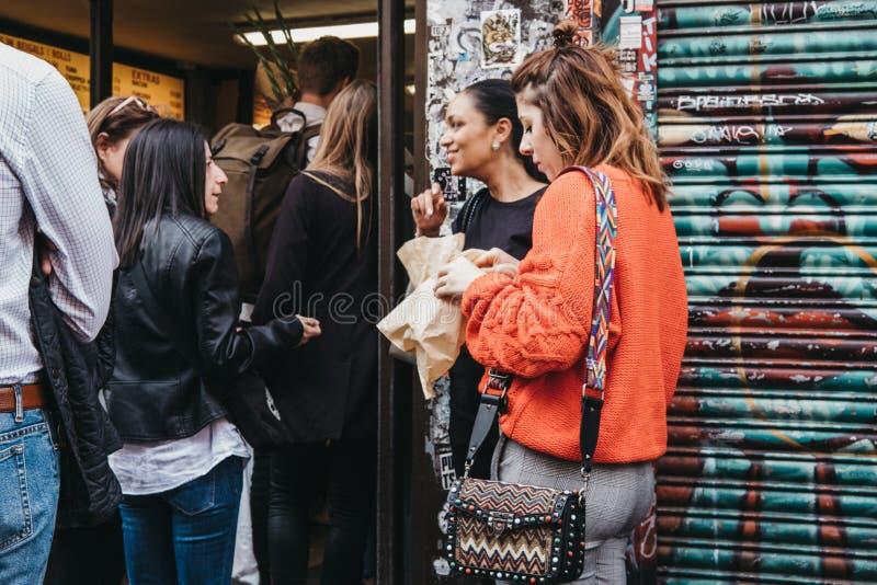 Les gens mangeant et faisant la queue pour acheter des bagels d'un Beigel célèbre font des emplettes dans la ruelle de brique, Lo image libre de droits