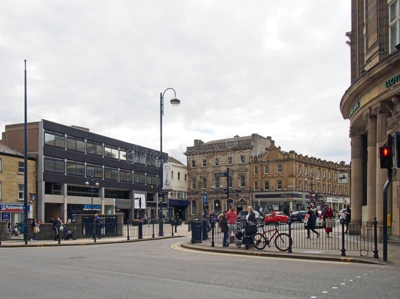 Les gens marchant au centre de ville de Huddersfield West Yorkshire pr?s de la croix historique du march? sur le coin du westgate photographie stock